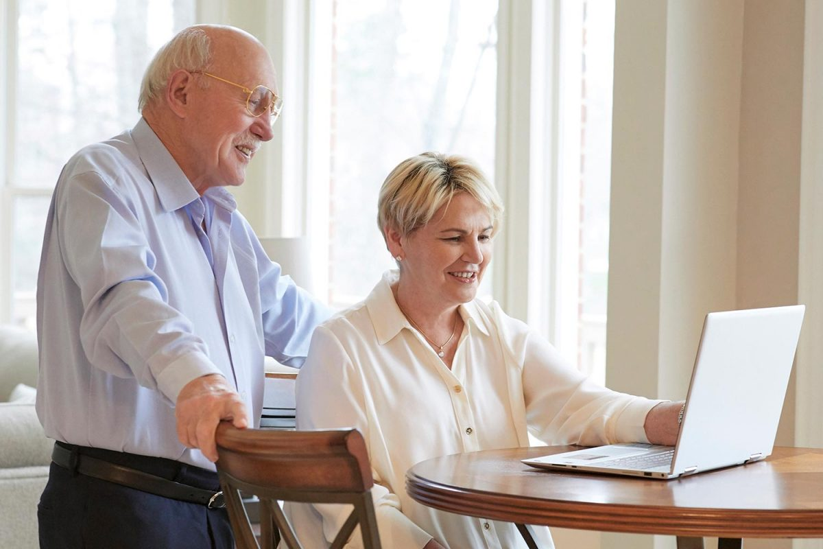 Editorial lifestyle photography of a smiling elderly couple using a laptop at their kitchen table