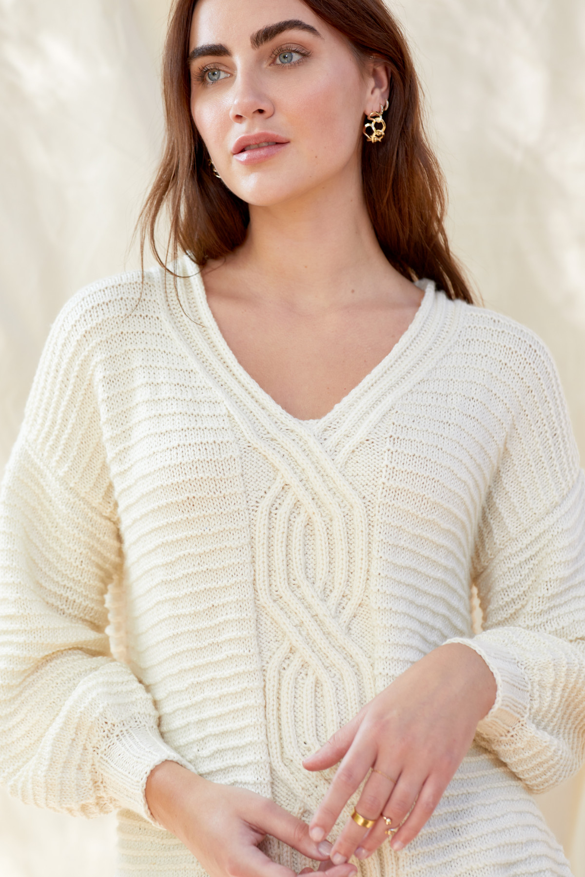 Editorial fashion photography of a dark haired female model wearing an ivory colored knit sweater