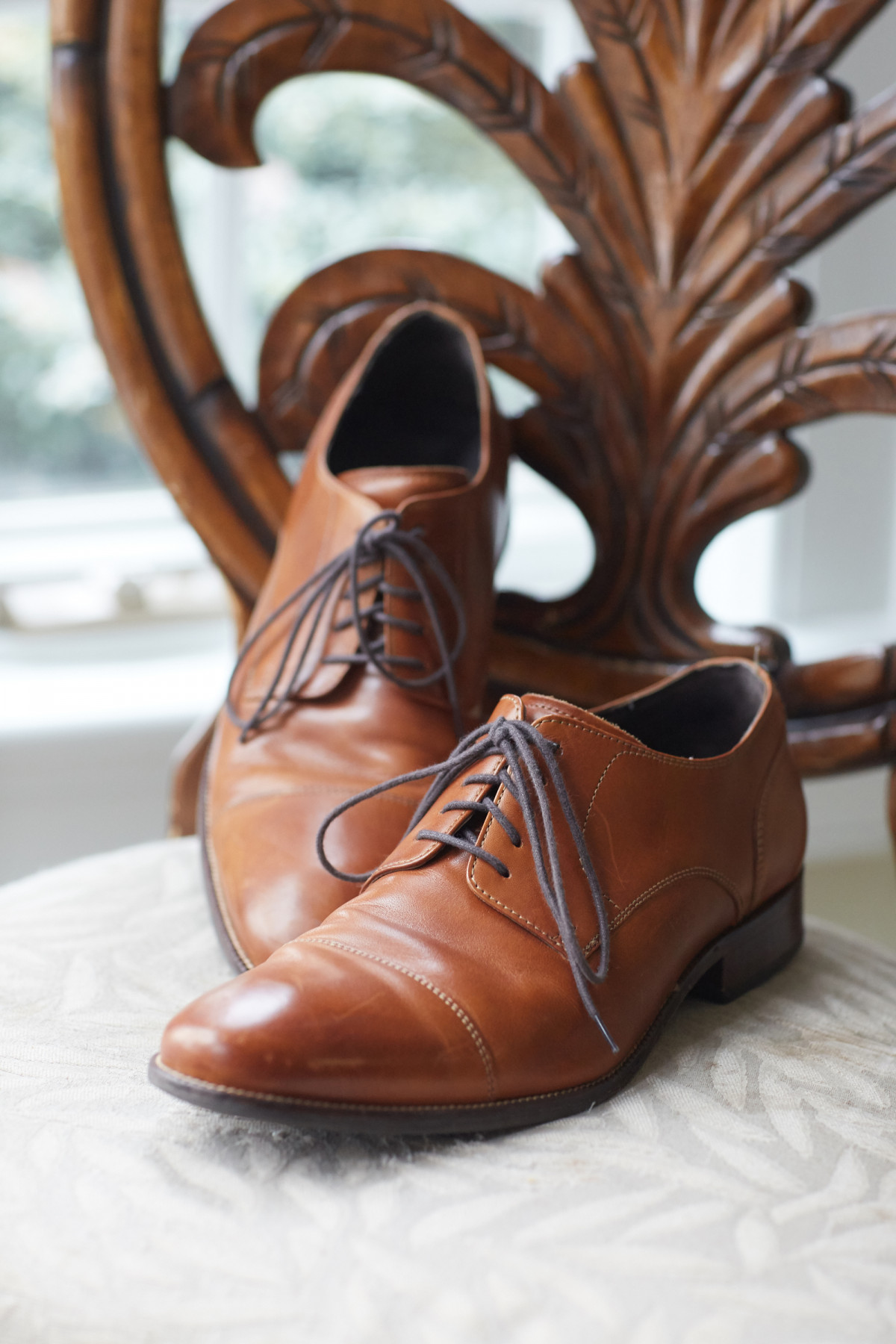 Editorial photo a pair of men's brown leather shoes placed on a cushioned dining chair
