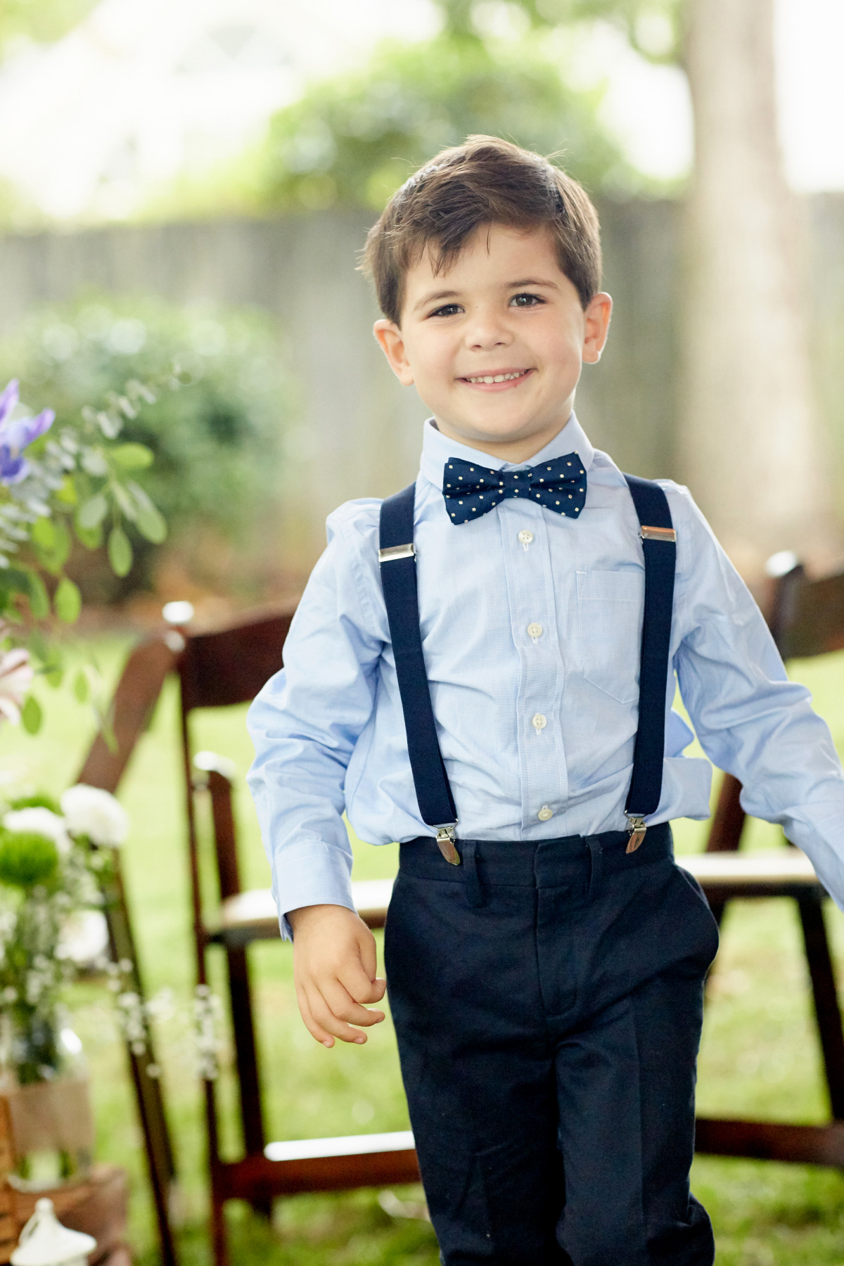 Editorial photo of a young boy dressed up in suspenders and a bow tie