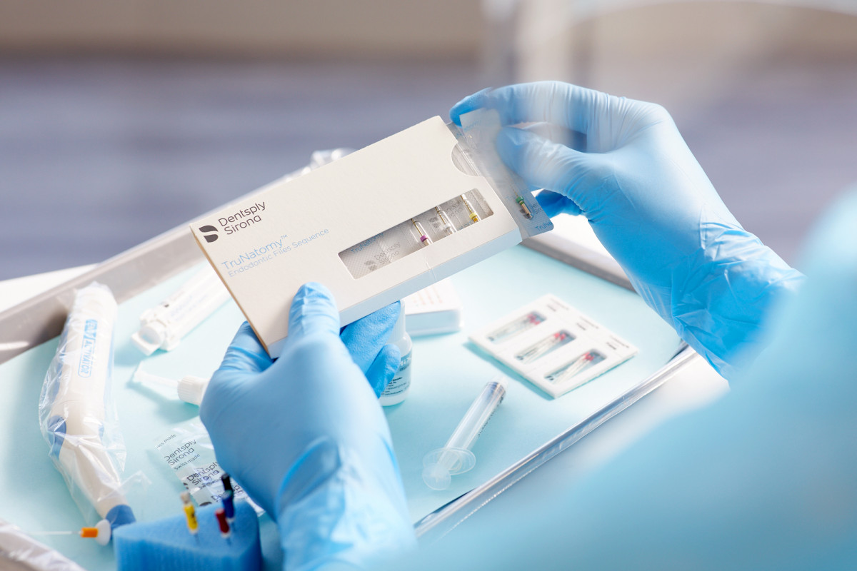 Lifestyle product photography of a healthcare worker's gloved hands opening a Dentsply TruNatomy testing kit