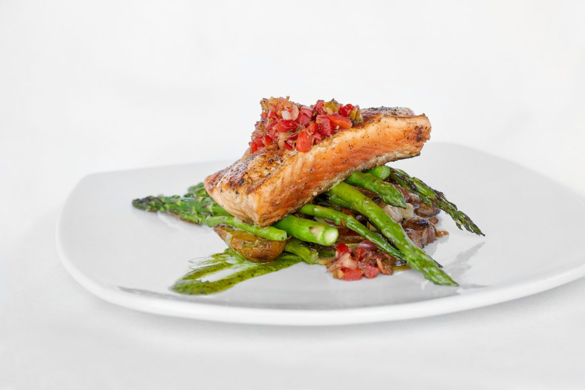 Restaurant food photography of grilled fish on top of a bed of green asparagus