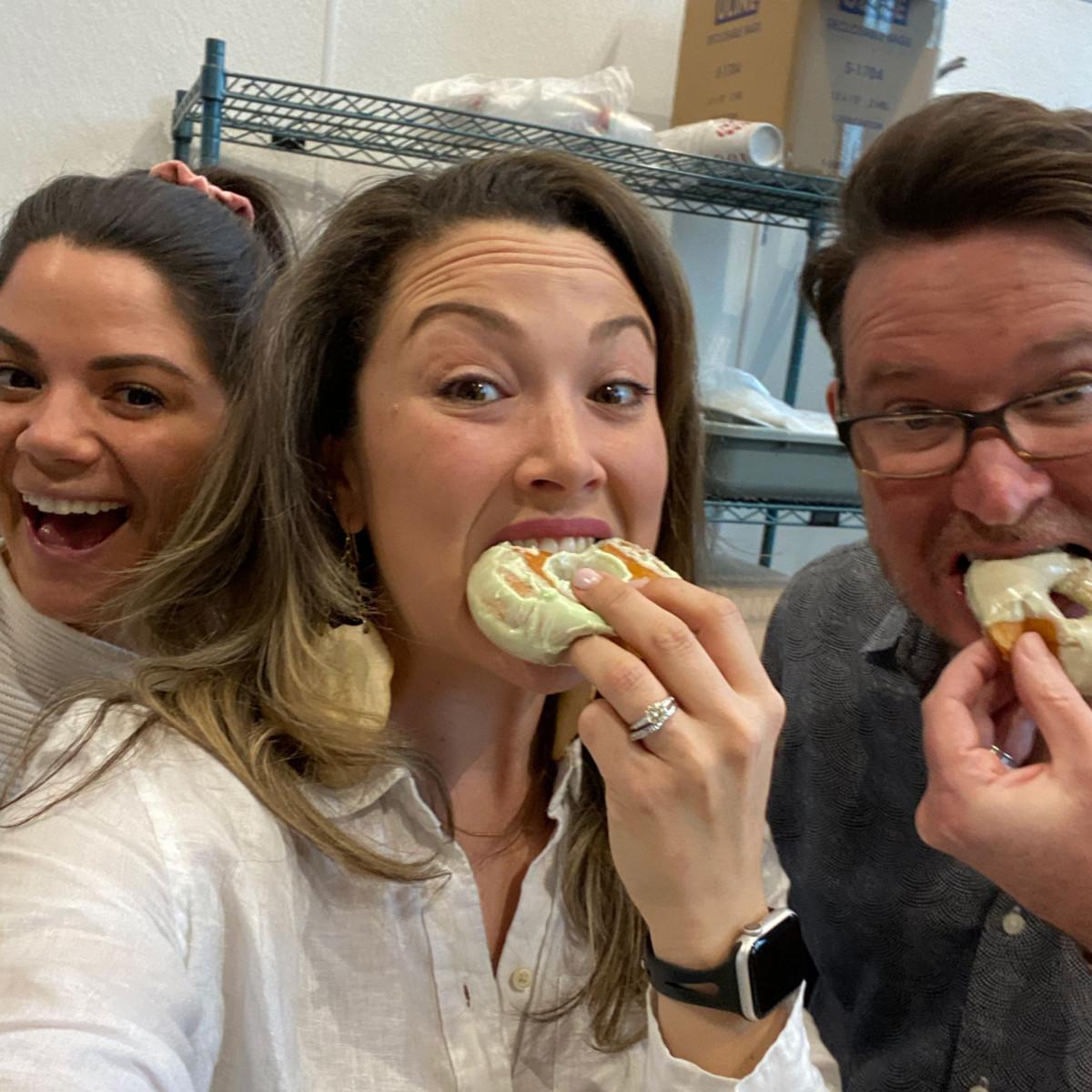 Candid photo of Salt Paper Studio team members eating doughnuts together