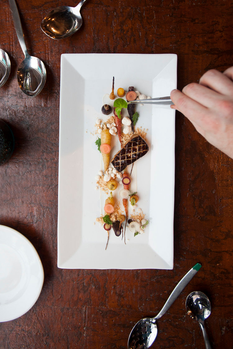 Lifestyle food photography of a person using tweezers to plate a modern dish