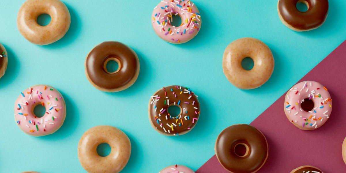 Mini Krispy Kreme doughnuts of various colors set on a colorful background