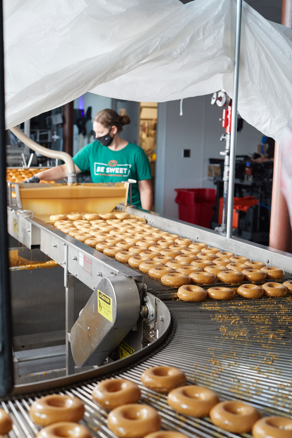 Doughnut glazing production line at Krispy Kreme Doughnuts