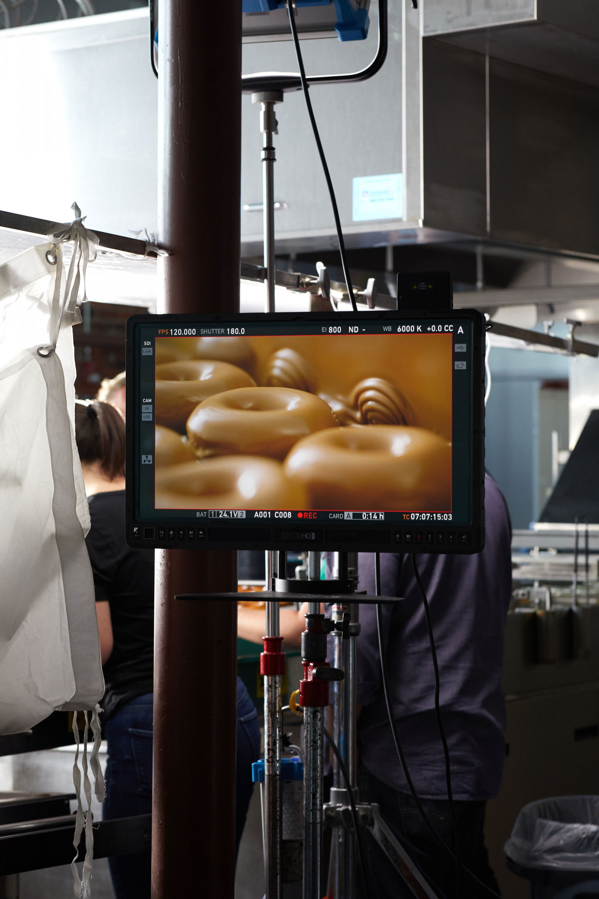 Behind the scenes on a professional food photography shoot showing digital display of doughnuts being photographed