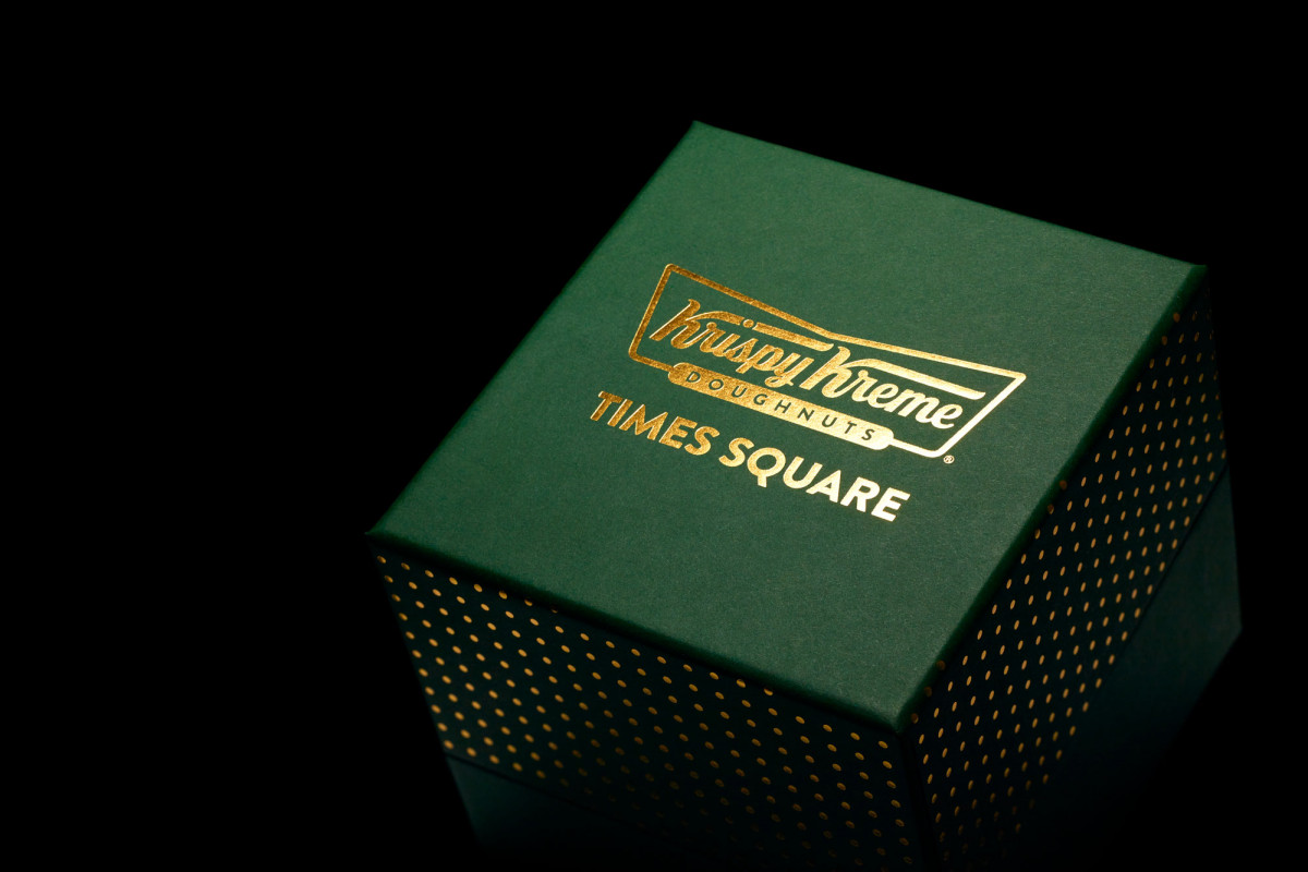 Sleek green box with gold lettering that says Krispy Kreme Doughnuts Times Square