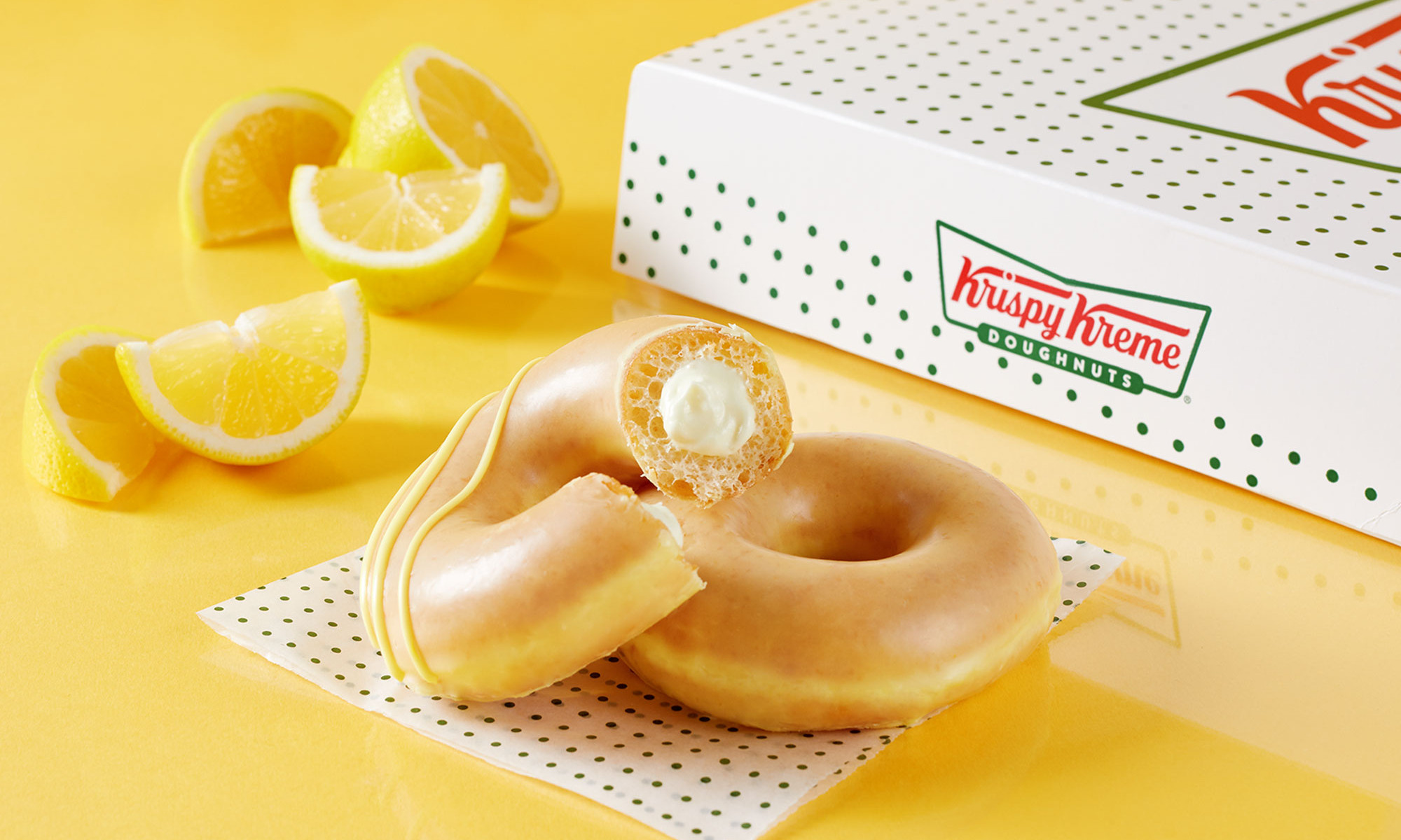 Professional commercial photography of lemon glazed Krispy Kreme doughnuts against yellow backdrop