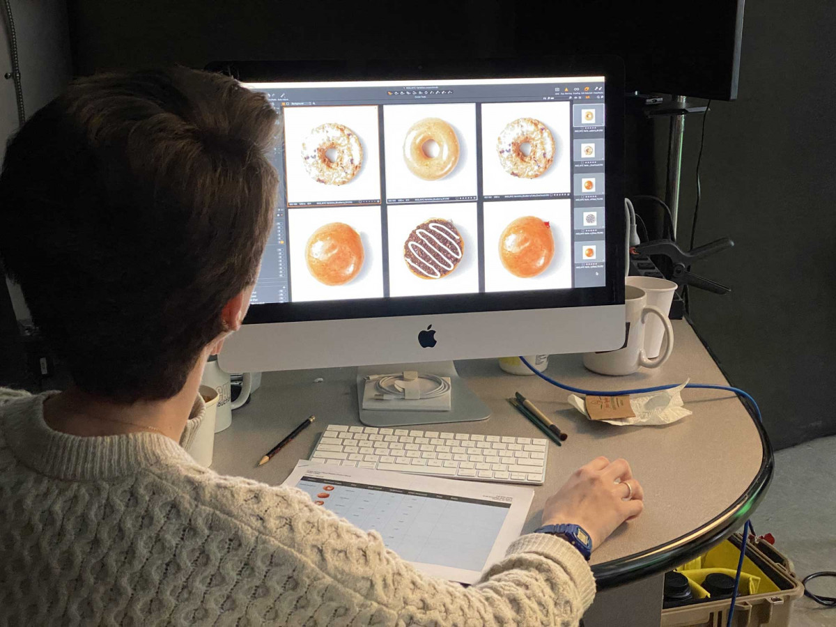 Professional photographer editing food product photos of doughnuts