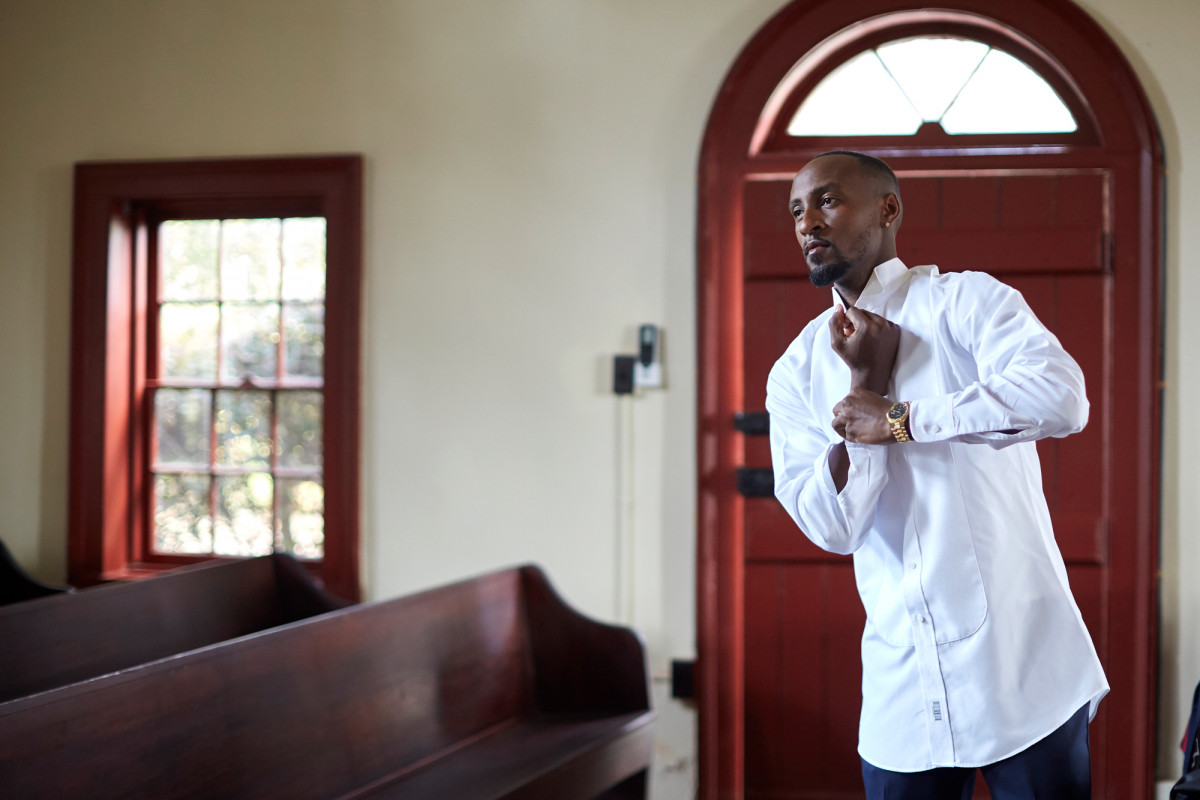 Editorial lifestyle photo of a man in a church buttoning his shirt cuff