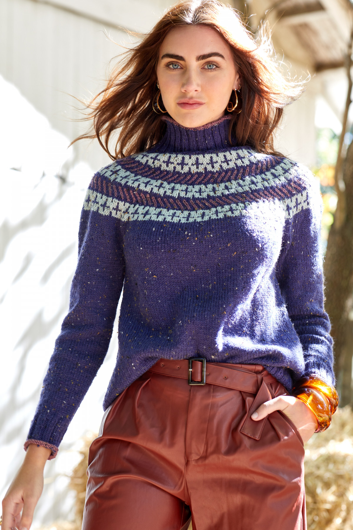 Editorial fashion photography of a female model wearing a dark blue knit sweater