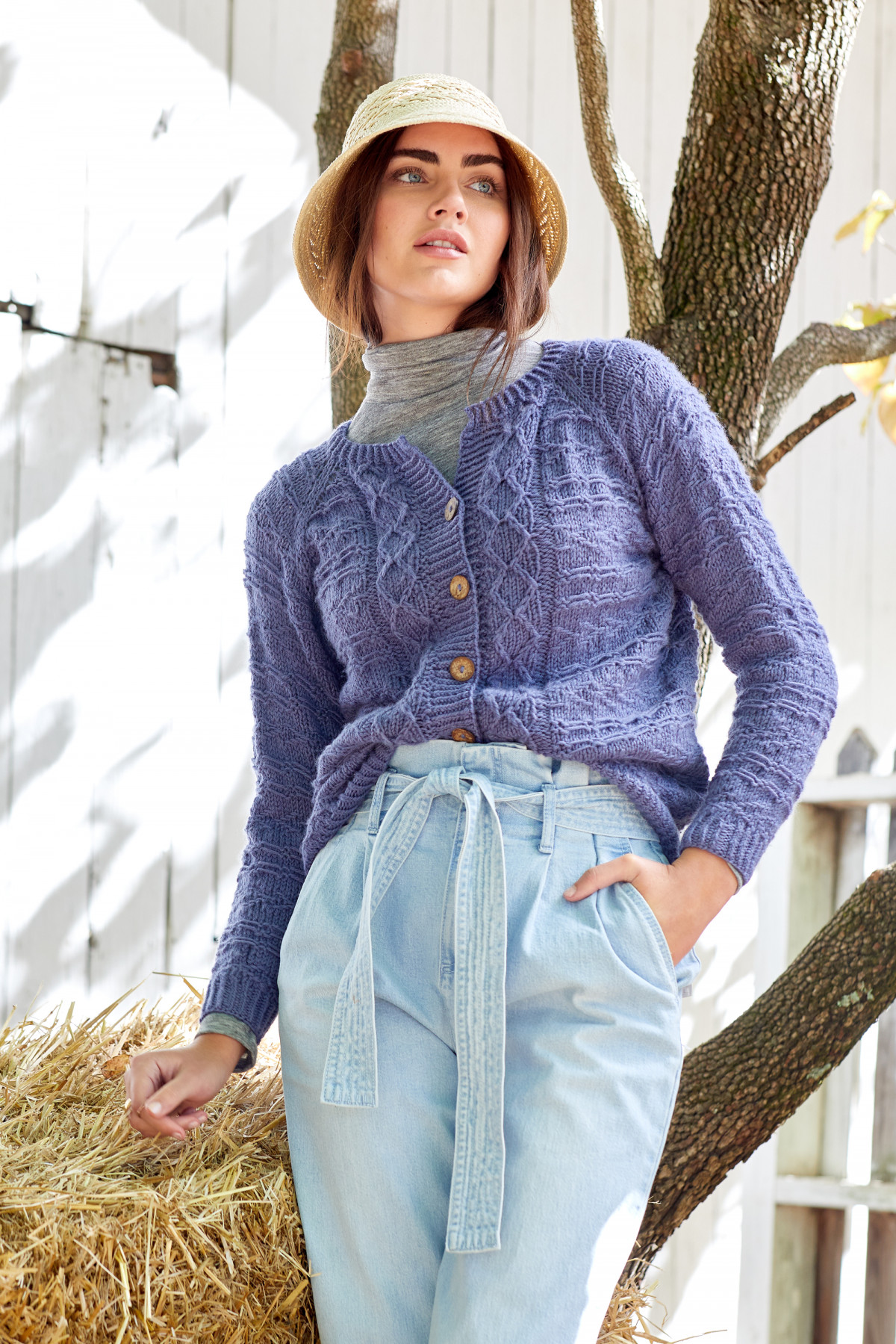 Editorial fashion photo of a female model wearing a straw hat and chunky purple knit cardigan