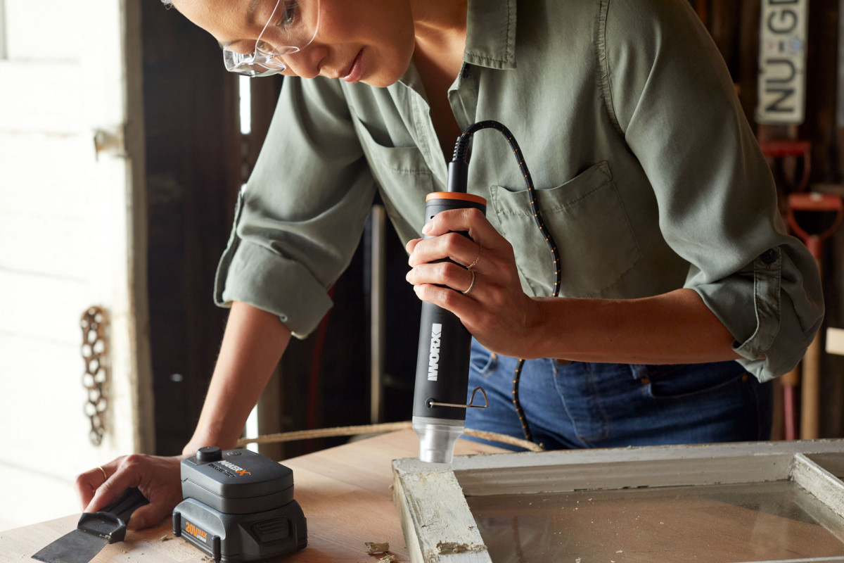 Lifestyle product photography of woman using a WORX tool to remove paint from a window frame