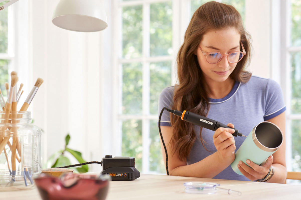 Commercial lifestyle product photography of woman using a MakerX tool to etch a design on a coffee tumbler