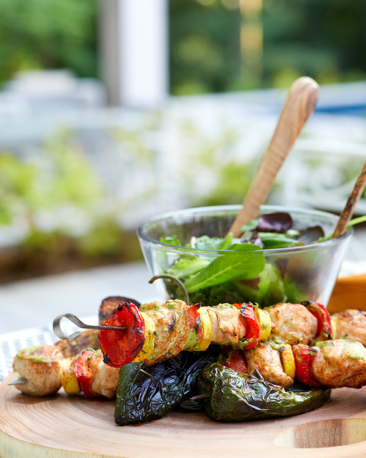 Food lifestyle photography of a plate of kebabs and mixed greens on a wooden serving board on an outdoor table