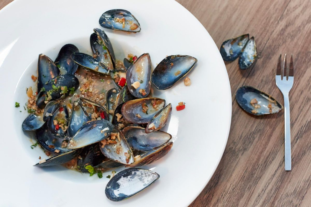 Food lifestyle photography of a white plate full of prepared mussels sitting on a wooden table