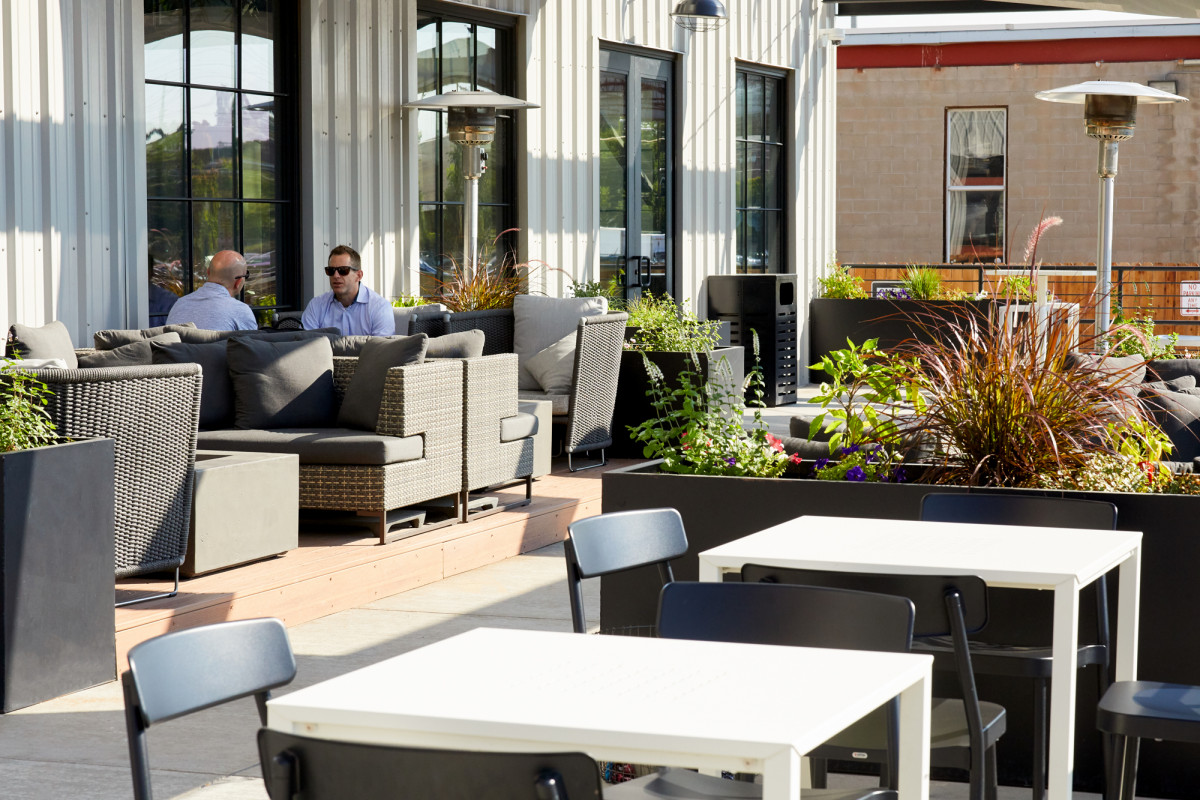 Commercial corporate photography of two men conversing at an outdoor patio table