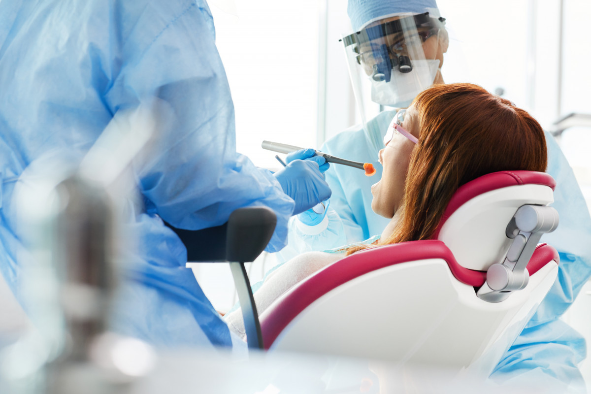 Commercial lifestyle photography of a woman undergoing a dental procedure by two healthcare workers in PPE