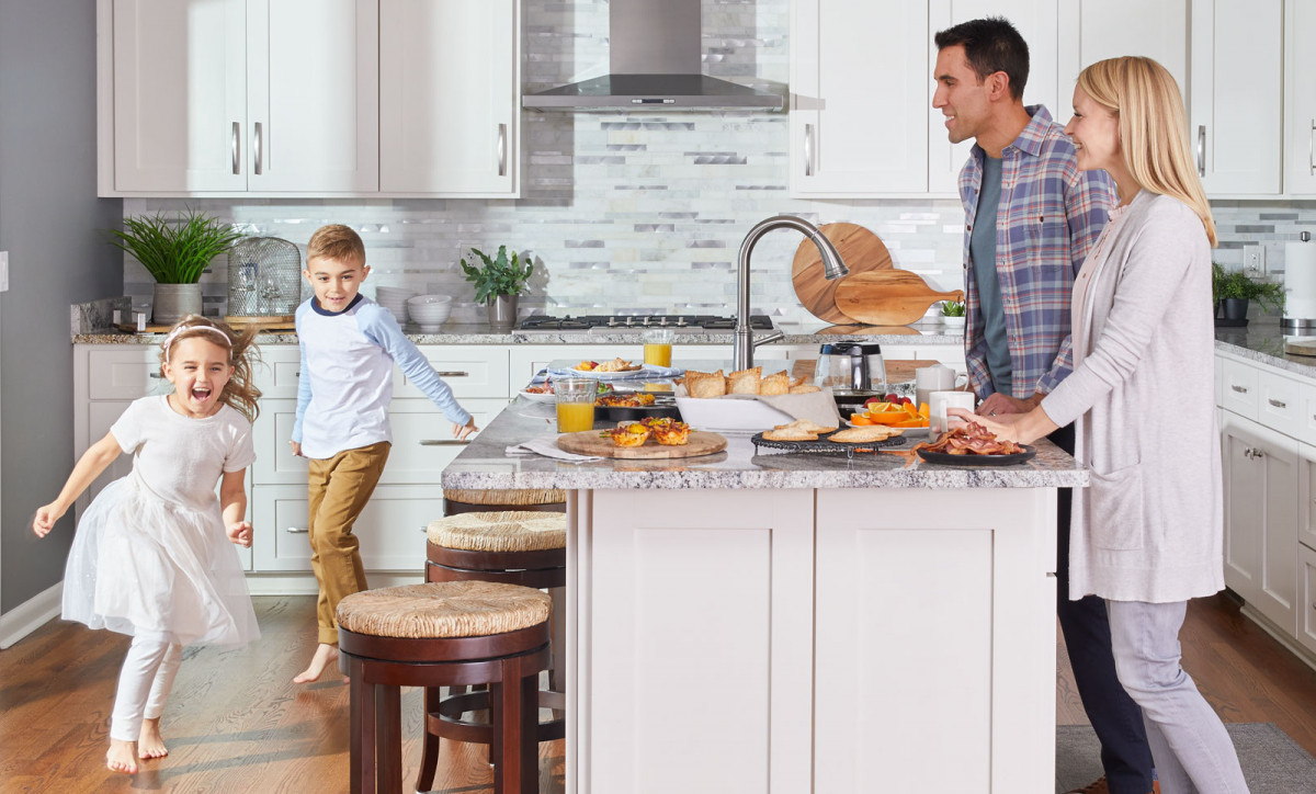 Lifestyle photo of family with two young children getting ready to have breakfast in their kitchen
