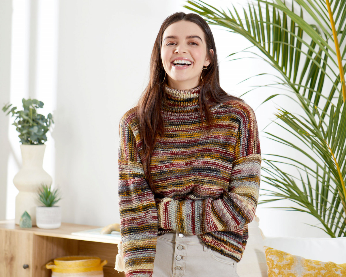 Lifestyle product photography of a young woman wearing a colorful knit sweater