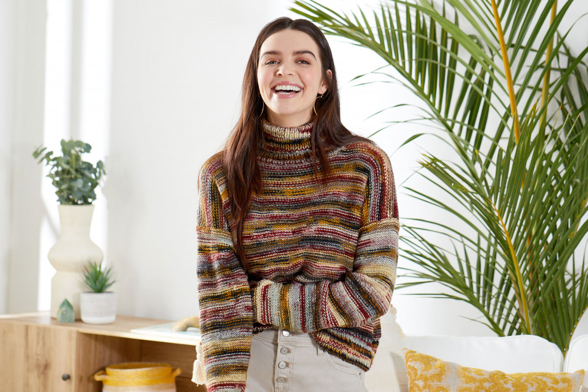 Lifestyle product photography of young woman wearing a multi-color knit sweater