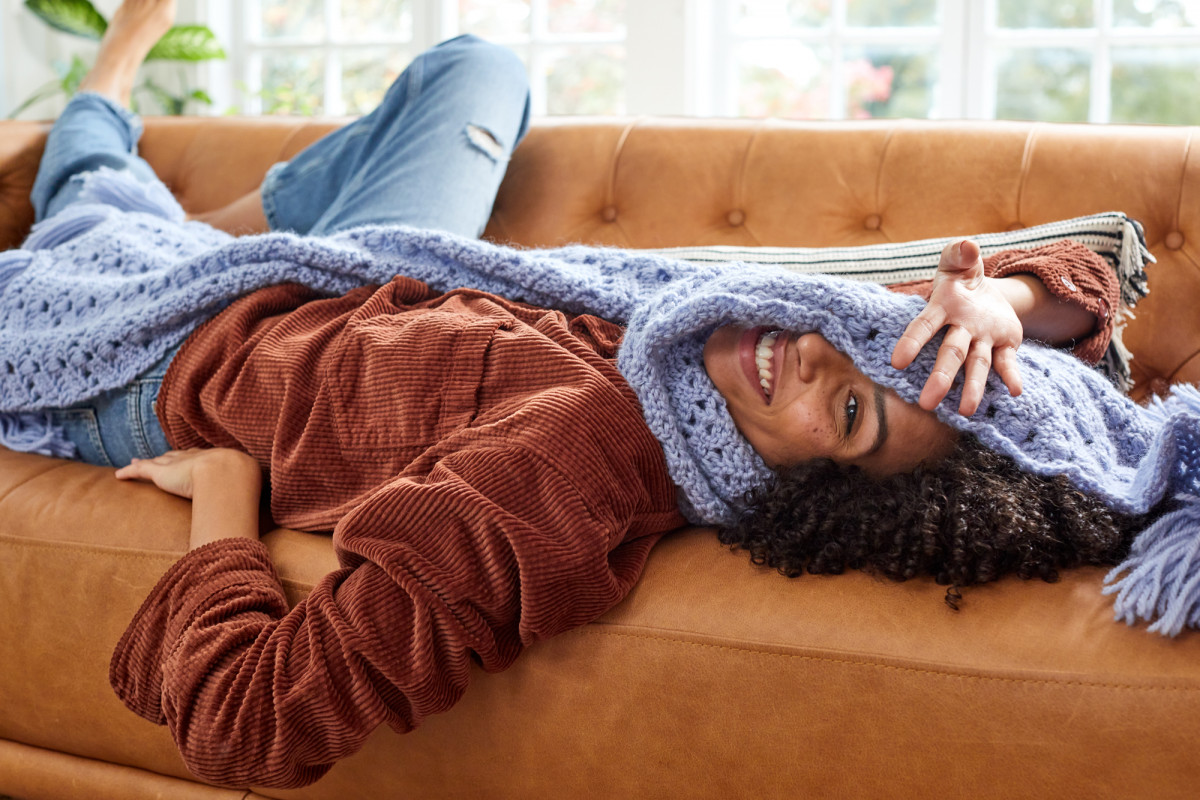 Editorial lifestyle photo of a woman lying on a couch wearing a hand knit blue scarf