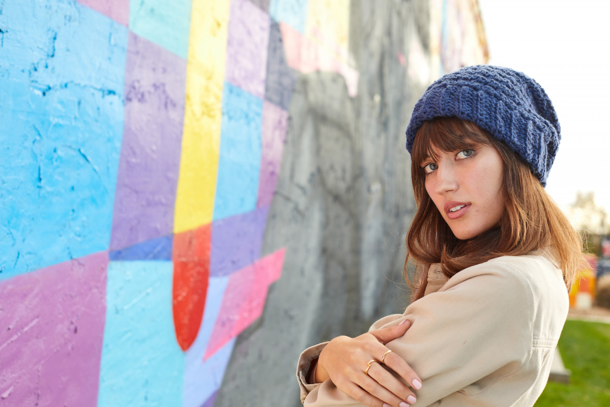 Editorial fashion photography of a female model wearing a knit blue cap standing next to some street art