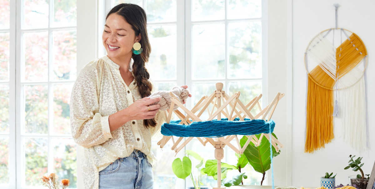Editorial photo of a smiling woman winding blue yarn