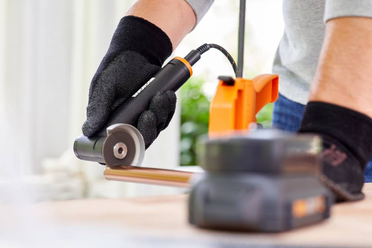 Lifestyle product photography of person using a WORX angle grinder to cut a pipe