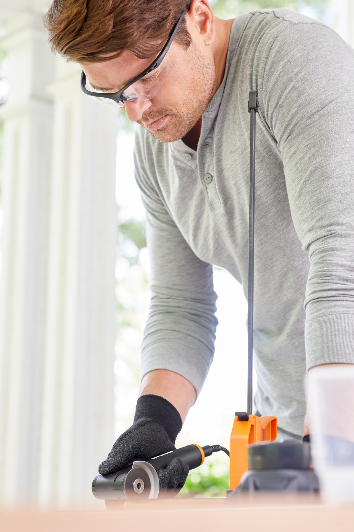 Lifestyle photography of man in gray shirt and safety goggles using an angle grinder by WORX