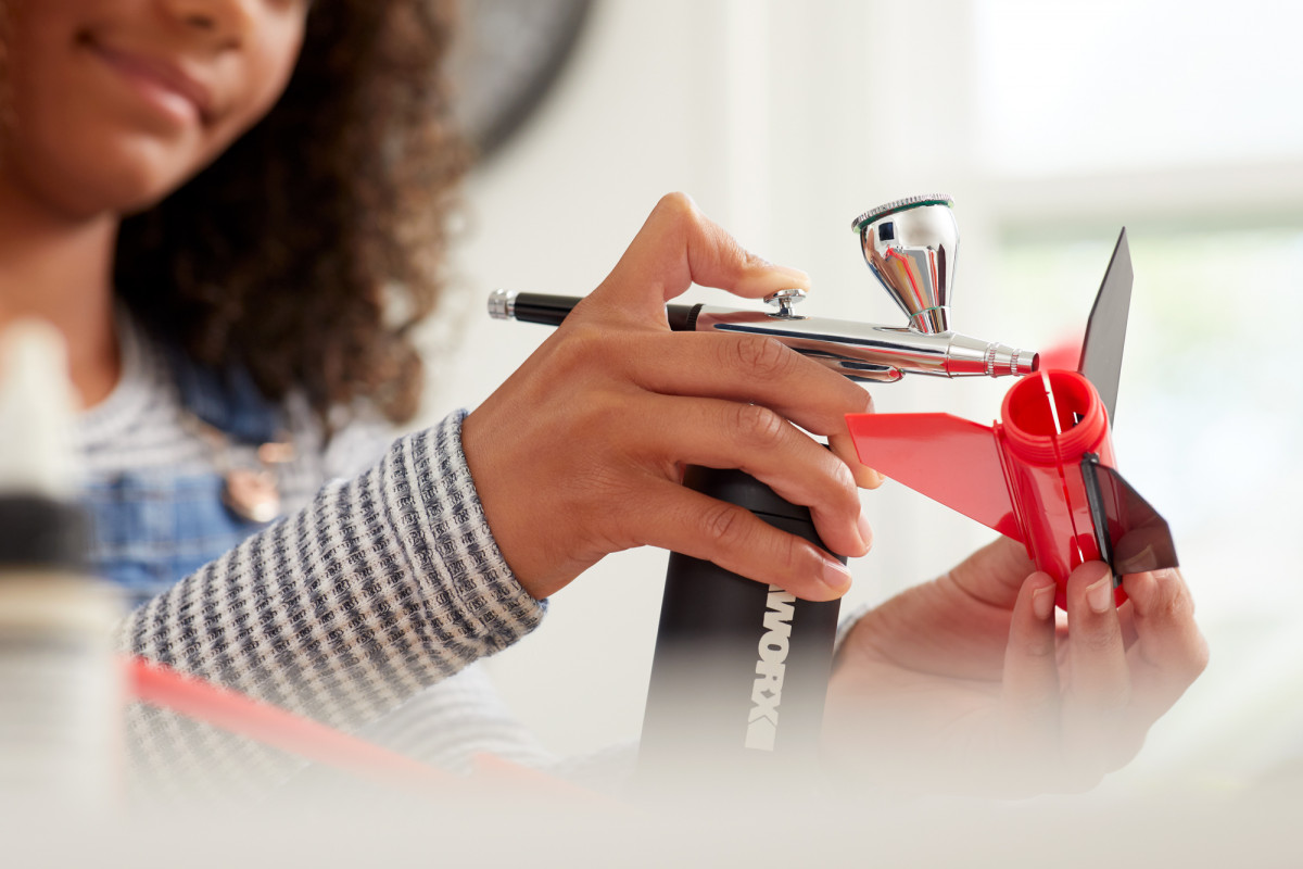 Lifestyle product photography of a woman using a small WORX airbrush to paint a toy