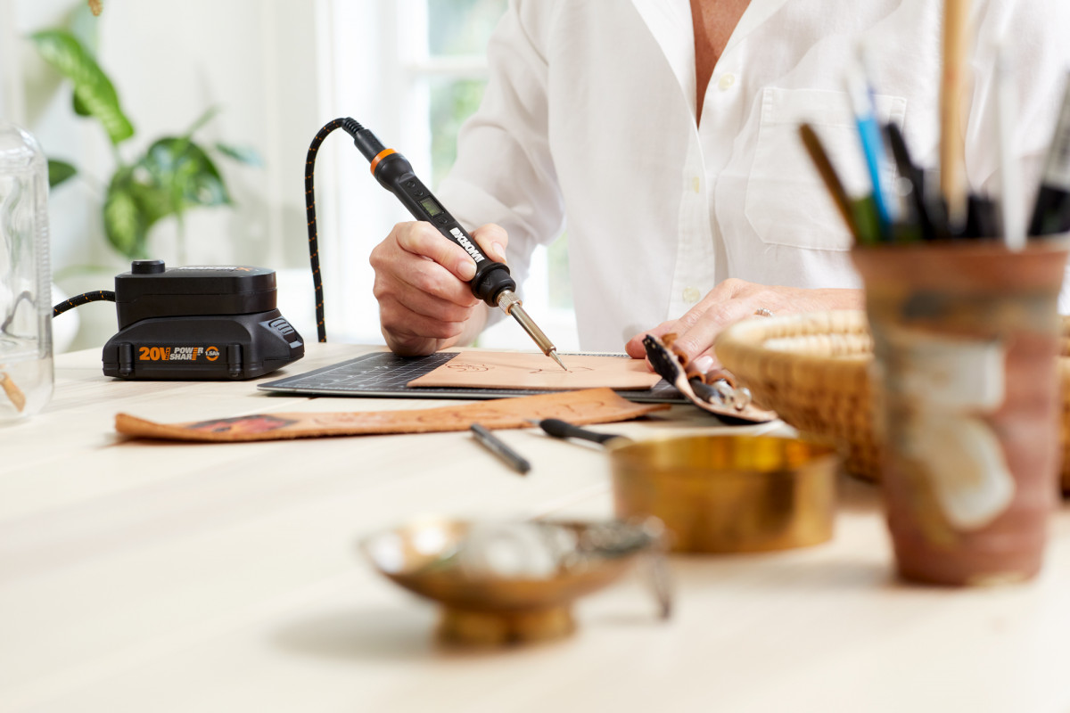 Lifestyle product photography showing a woman using a small WORX tool to etch designs on a piece of leather