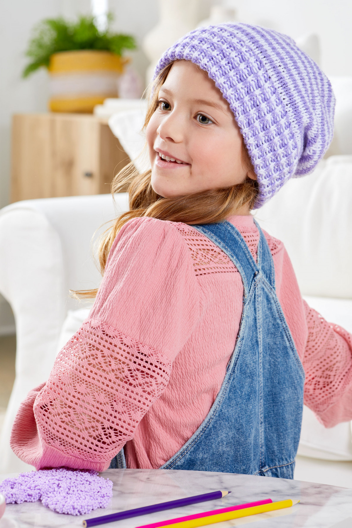 Lifestyle product photography of young girl wearing a hand knit purple cap