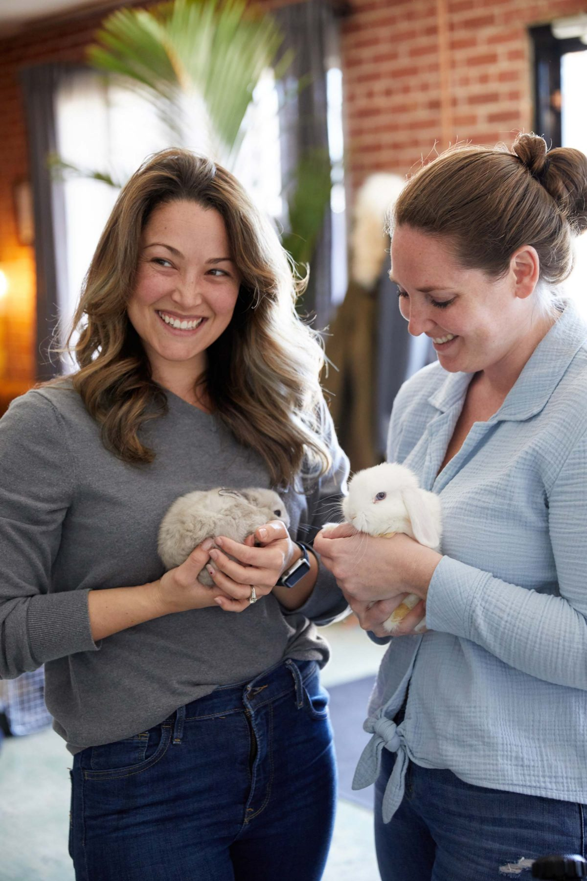 Two smiling women holding white bunnies