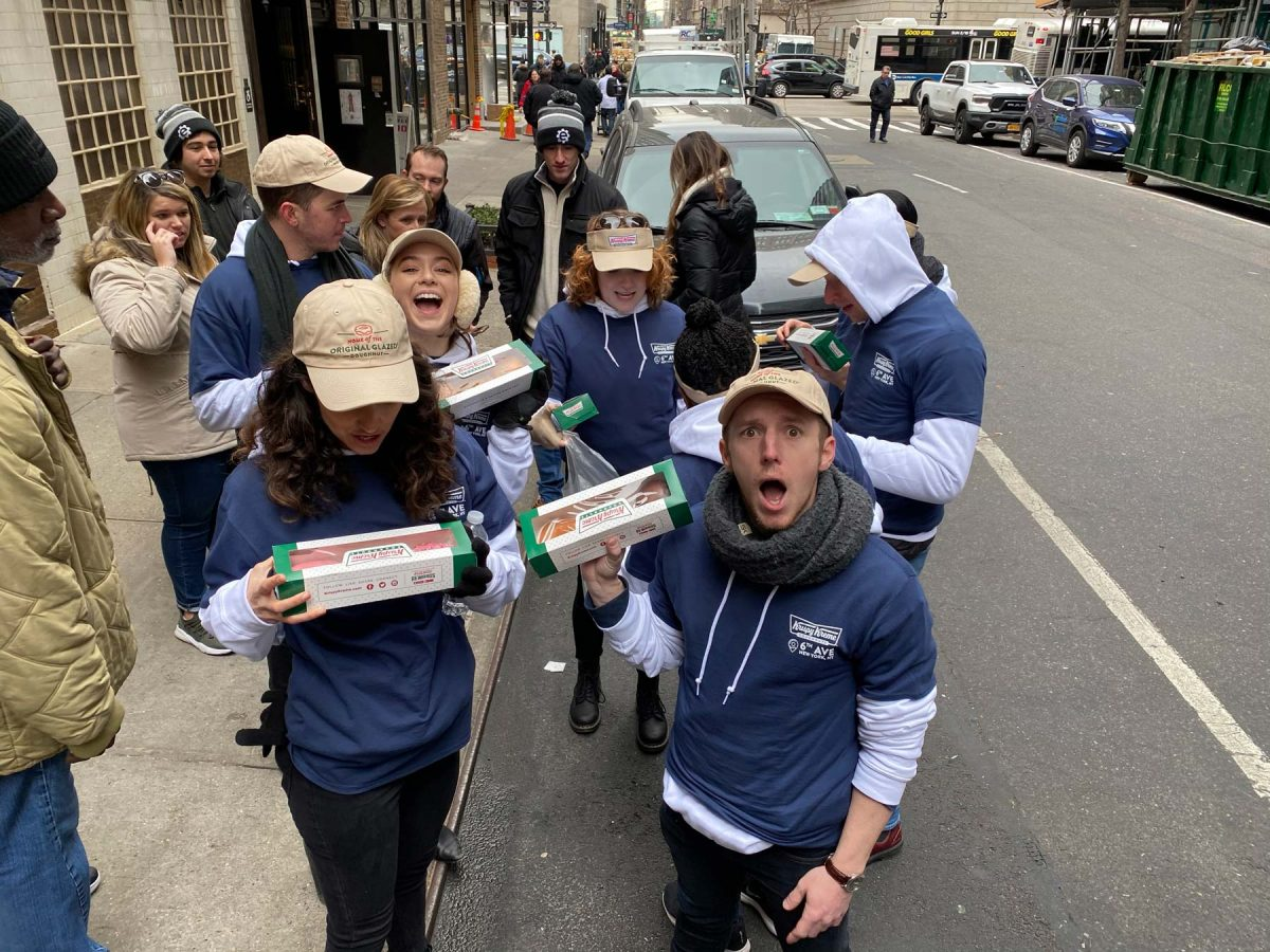 Krispy Kreme Doughnuts employees holding boxes of doughnuts in the street in NYC