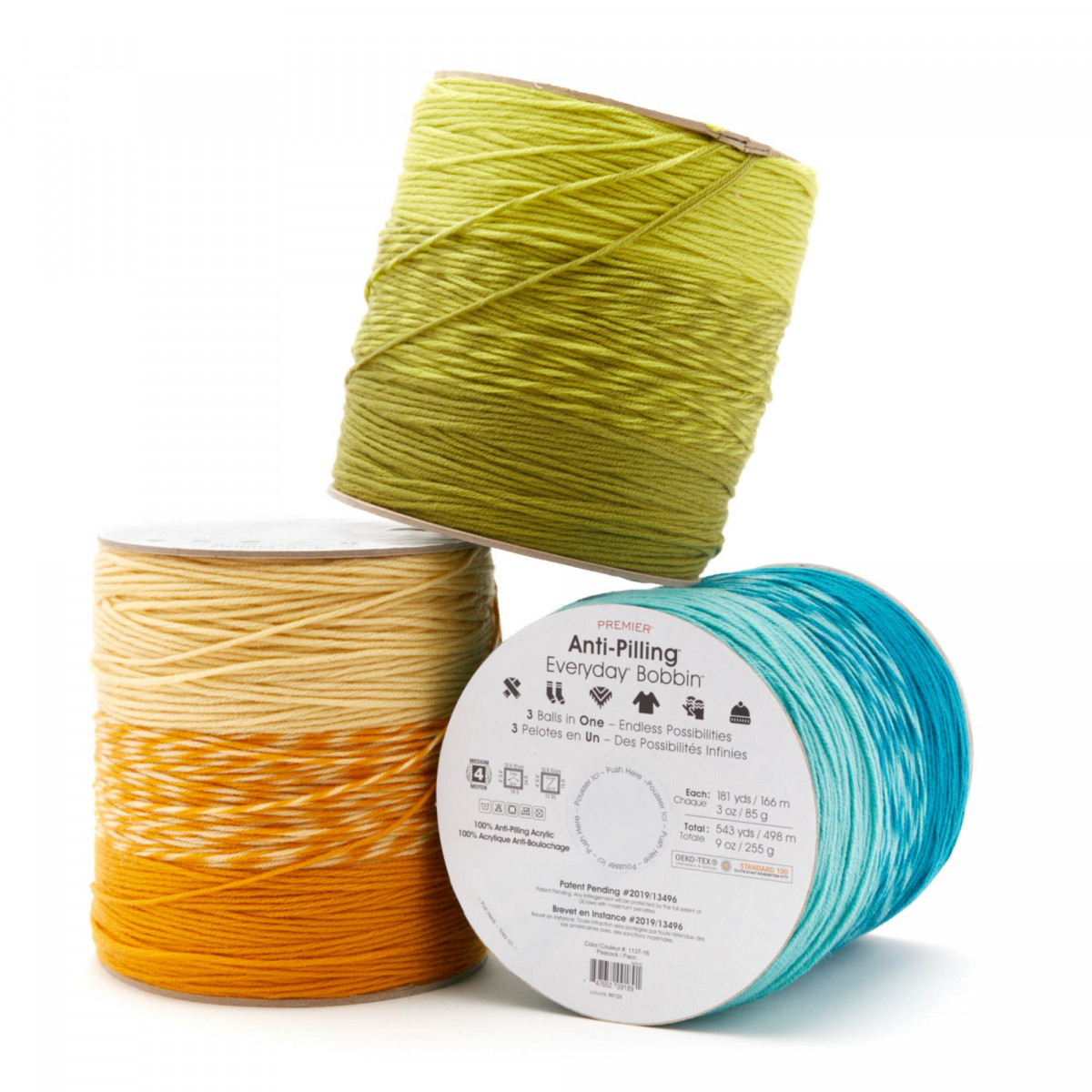 Product photography of three brightly colored bobbins of yarn