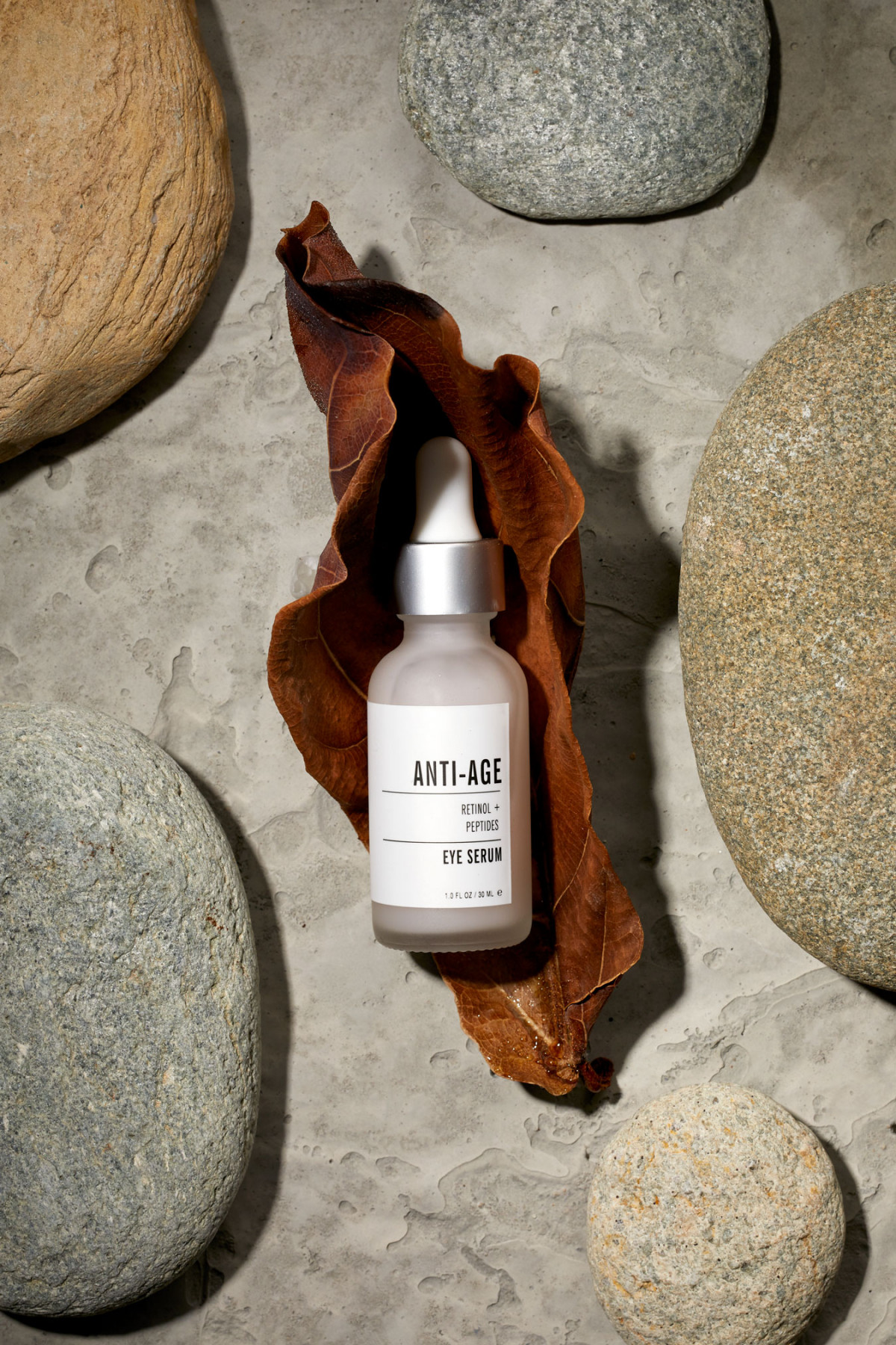 Commercial product photography of anti-aging eye serum amidst natural elements