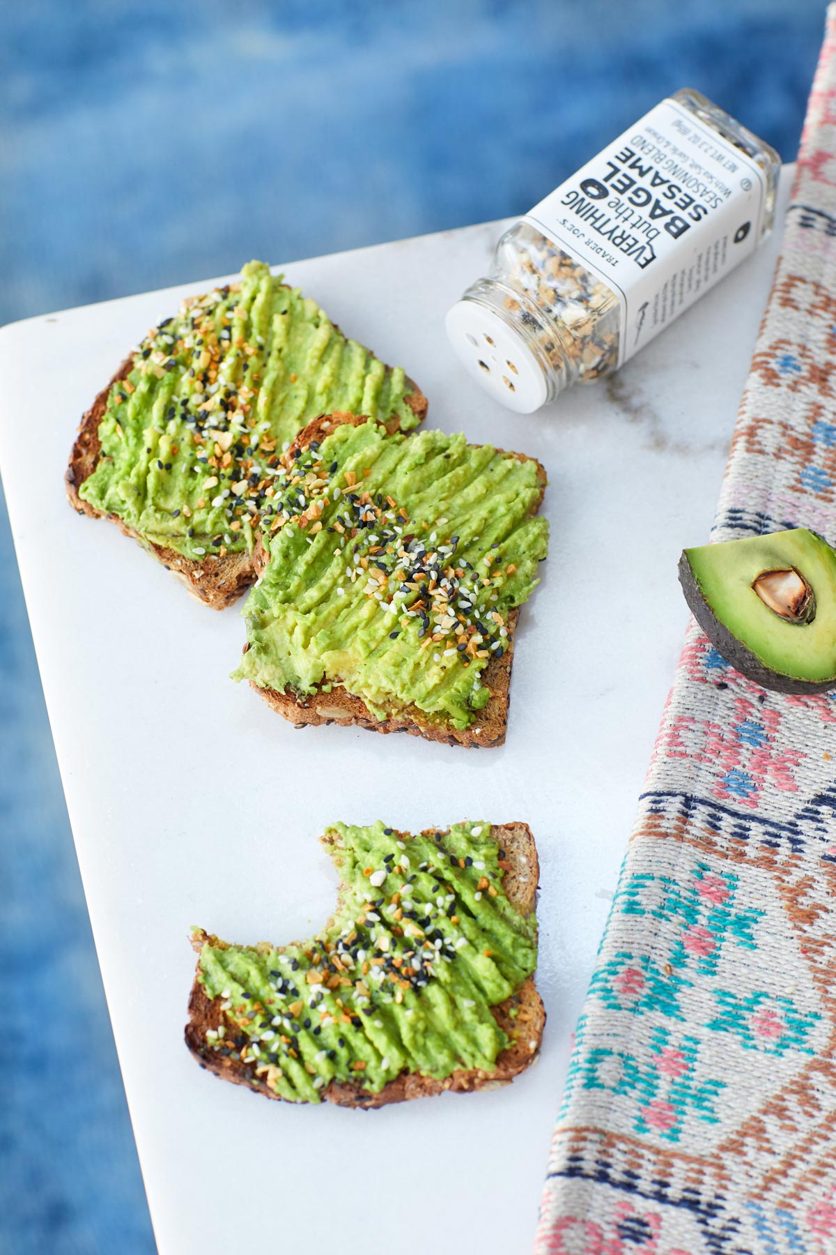 Food lifestyle photography of colorful avocado toast on a white cutting board next to a bottle of seasoning salt
