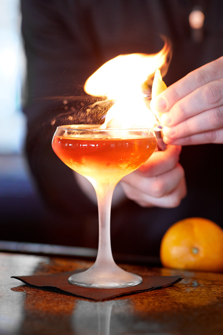 Food lifestyle photography of a bartender lighting a cocktail on fire