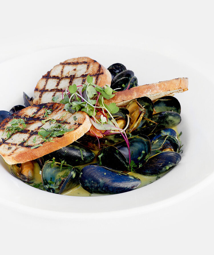 Restaurant food photography of black shelled mussels in broth served with toasted bread
