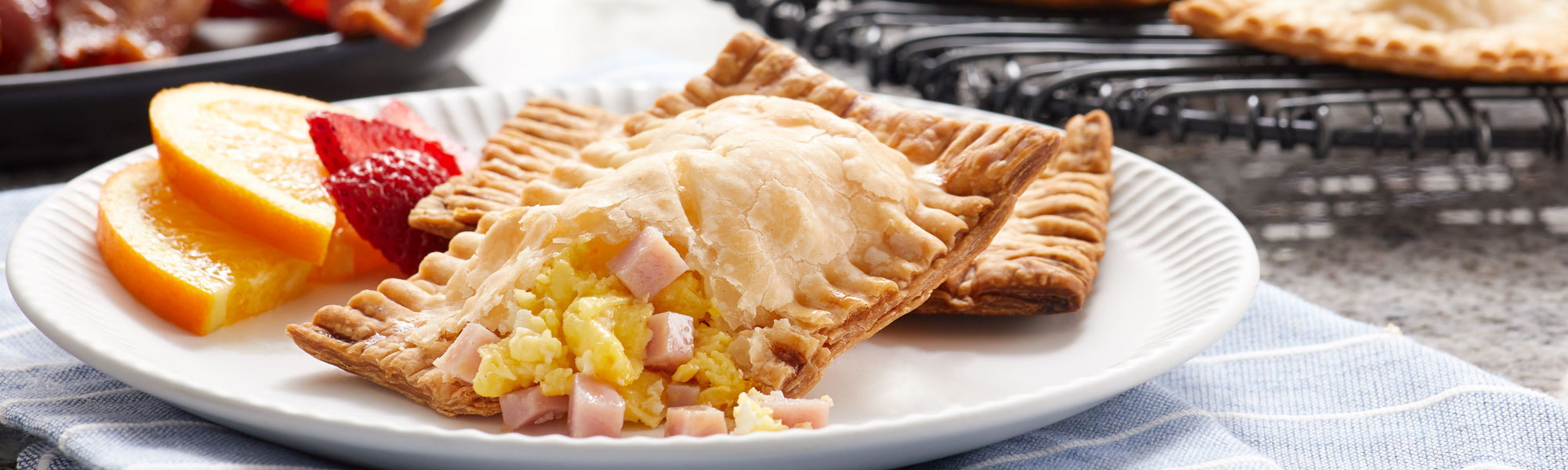 Food lifestyle photo of golden breakfast pastry filled with scrambled eggs and Smithfield ham