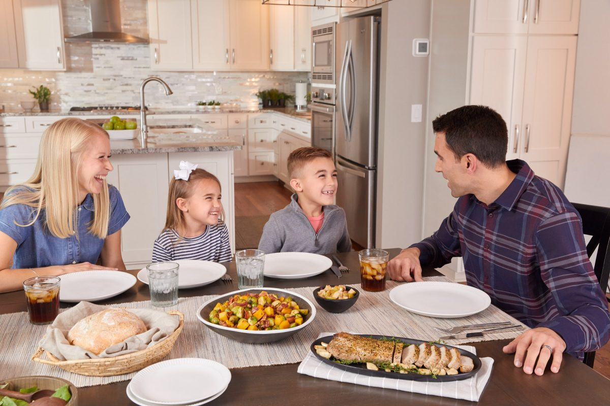 Commercial lifestyle photography of a young family sitting at the dinner table with a Smithfield pork tenderloin