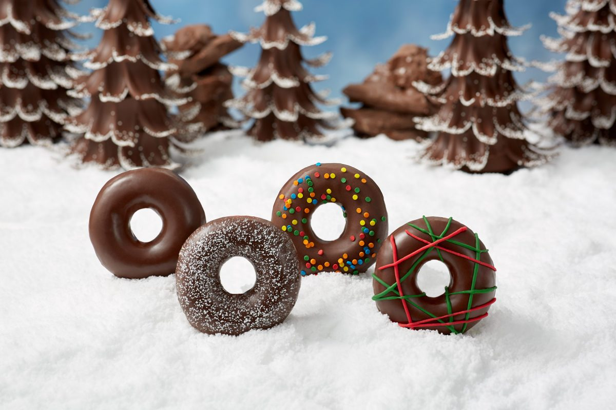 Commercial food product photography of holiday themed Krispy Kreme doughnuts set in a snowy landscape with chocolate Christmas trees