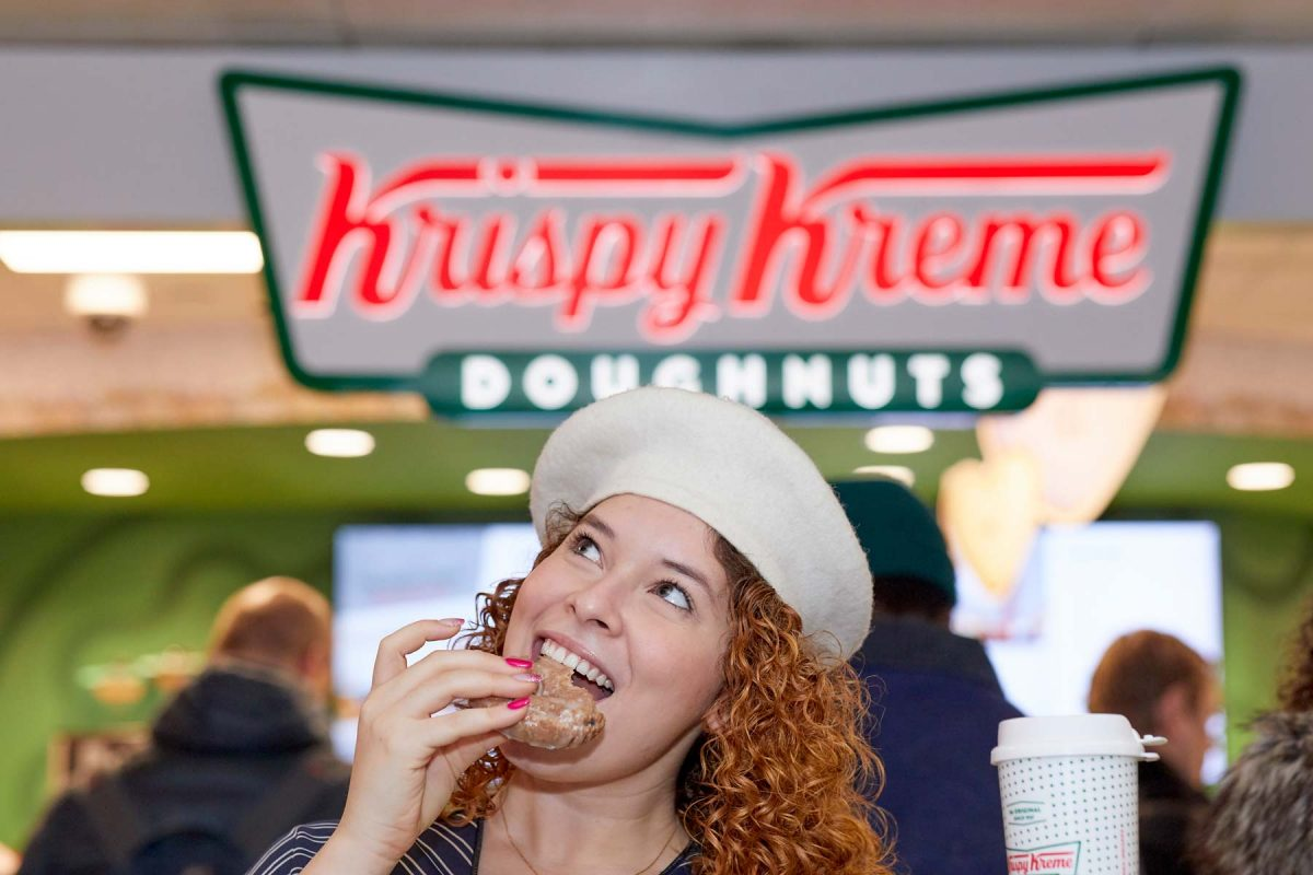 Corporate lifestyle photo of a woman eating a Krispy Kreme doughnut in front of a Krispy Kreme sign