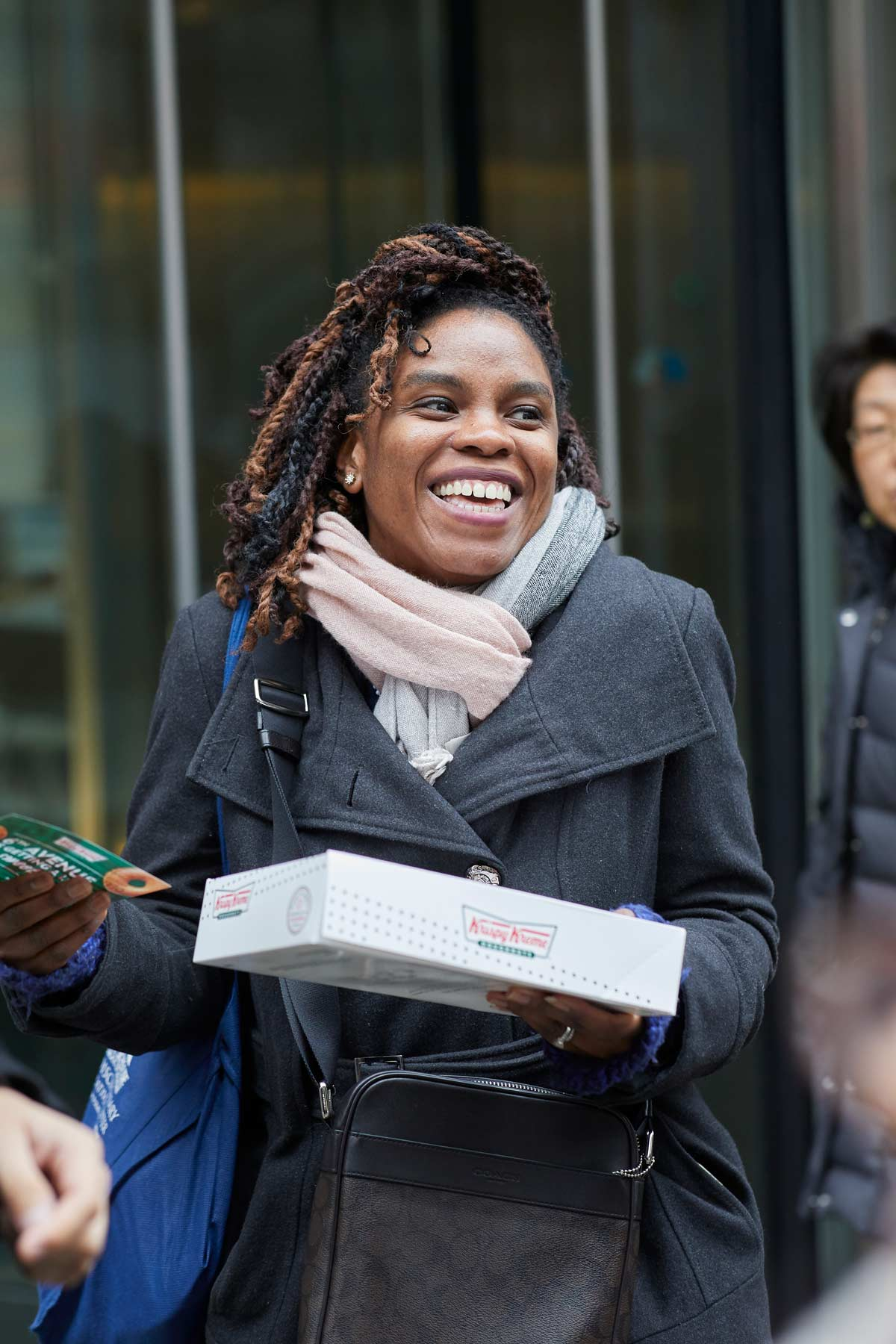 Commercial lifestyle photography of a woman carrying a box of Krispy Kreme doughnuts on the street