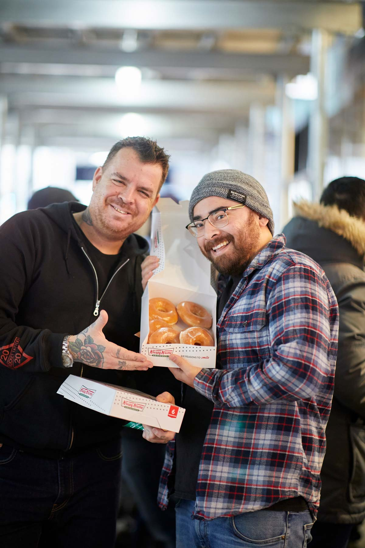 Commercial lifestyle photography of two male friends enjoying a box of Krispy Kreme doughnuts