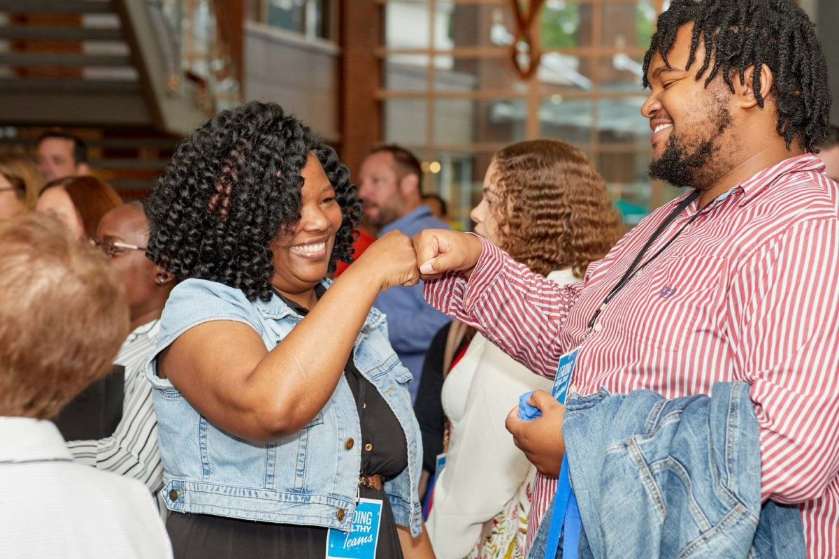 Corporate event photo of two people giving each other a fist bump in the middle of a crowd