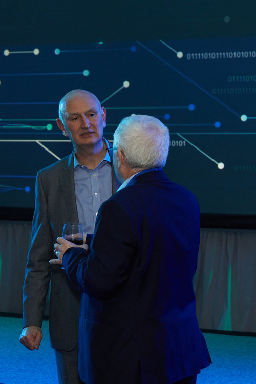 Corporate event photo of two older men having a conversation in a ballroom