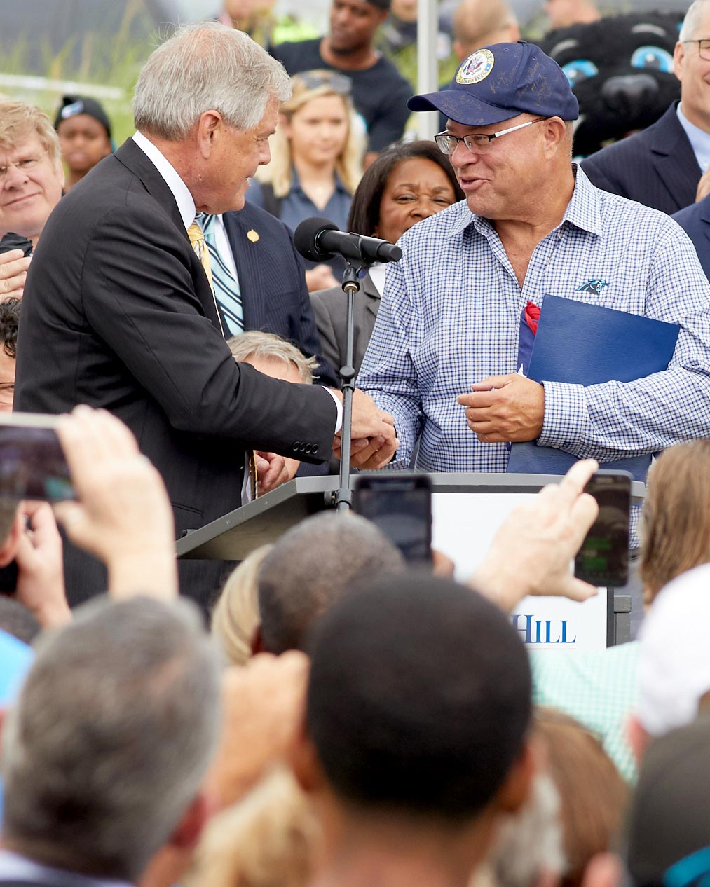 Politician shaking hands with a business owner at an outdoor event for the Carolina Panthers in Rock Hill, SC